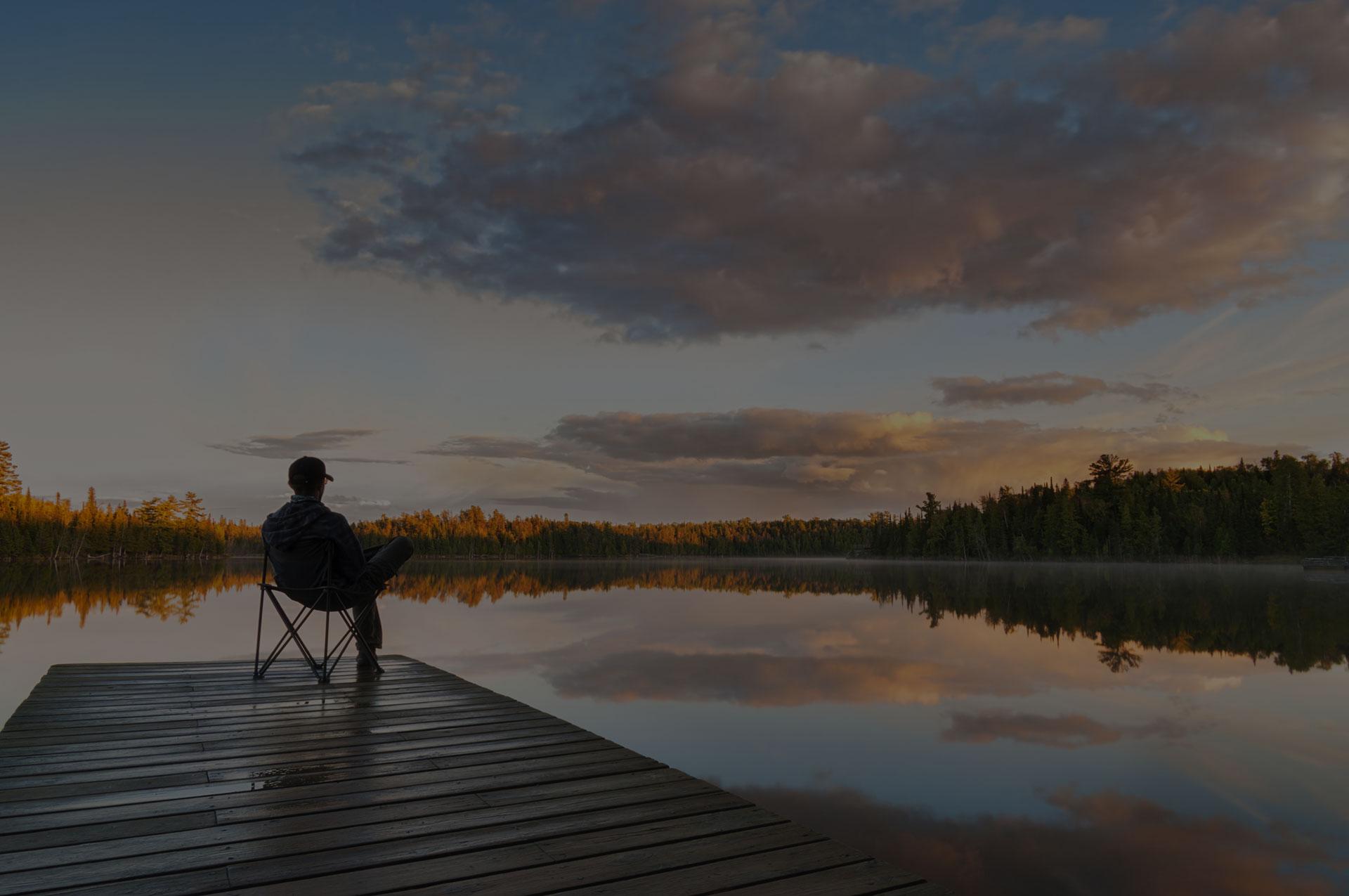 Man sitting on a lake pier at sunset
